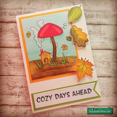 DIY Grußkarte mit coloriertem Herbsmotiv. RauchendesHäuschen unter einem Pilz. Fallende Blätter. Text: Cozy Days Ahead.