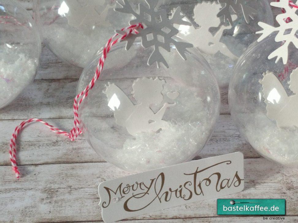 Acrylbaumkugeln mit ausgestanztem, weißen Engelmotiv und Kunstschnee innendrin. Außen eine ausgestanzte Schneeflocke.