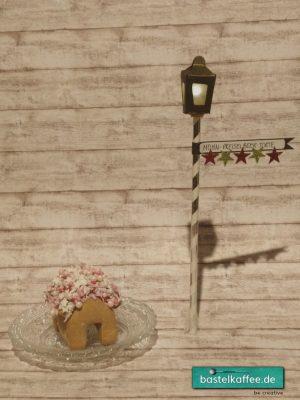 DIY Miniaturlaterne aus Tonkarton, Seidenpapier und Strohhalm. Beleuchtet mit einem Ballonlicht. Daneben eine kleines Lebkuchenhäuschen.