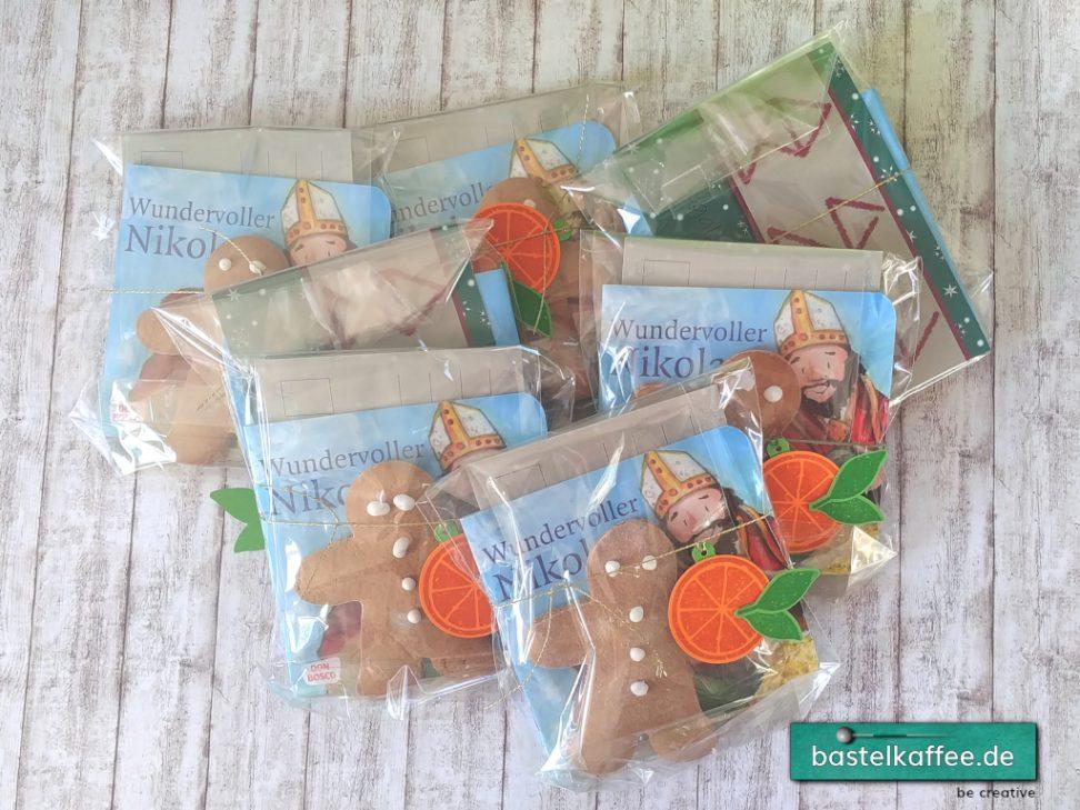 Nikolausgeschenk für Kinder. Pixi-Buch vom Nikolaus und Lebkuchenmännchen verpackt in einer transparenten Tüte. Dekoriert mit einer gestempelten und ausgestanzten Orangenscheibe.