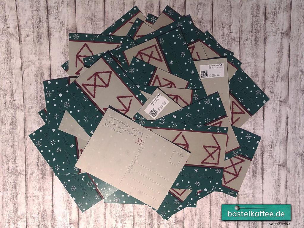 Ein Stapel Postkarten. Das Motiv sind drei unfertig gezeichnete Häuser vom Nikolaus. Text: Ach egal, Ihr wisst schon.