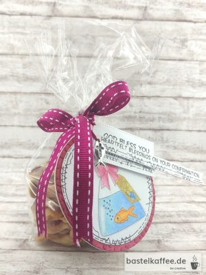 "Gold Fischli crackers giftbag. Tag with a colored digital stamp of an goldfish in a bag with water. Sayings: ""God bless you"" and ""Heartfelt blessings on your confirmation""."