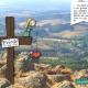 """Blick von einem Berg ins Tal auf Wälder, Wiesen und Dörfer. Auf dem Berg steht ein Kreuz auf dem ein Mädchen sitzt und ein Herz in der Hand hält. Am Kreuz hängt ein Schild, auf dem """"Friede sei mit euch"""" steht."""