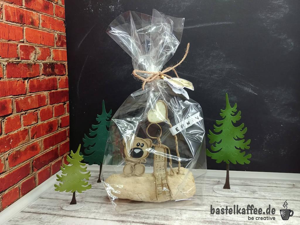 Papierdrahtfigur in Zellophantüte als Geschenk verpackt.