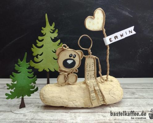 Papierdrahtfiguren basteln: Ein Junge sitzt neben einem Herz und umarmt seinen Teddy